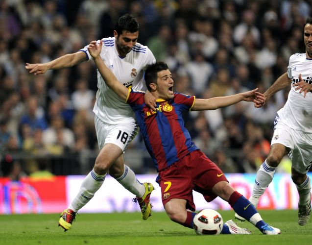 Raul Albiol puxa David Villa dentro da área e o árbitro marca pênalti