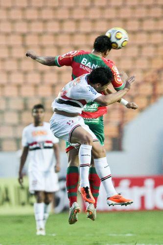 Henrique salta em disputa com defensor da Portuguesa. São Paulo venceu por 2 a 0 e foi para a semifinal do Paulista, quando enfrentará o Santos em casa