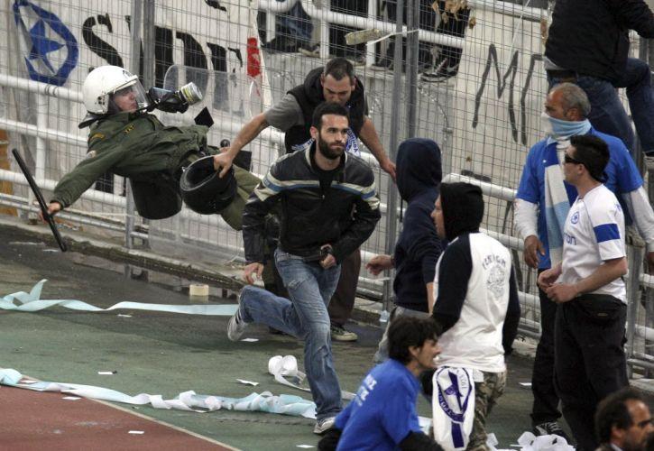 Policial grego tenta atingir um torcedor com uma rasteira durante a confusão generalizada que marcou a final da Copa da Grécia, vencida pelo AEK.