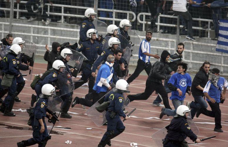Polícia avança em bloco contra torcedores gregos durante um confronto generalizado que marcou a final da Copa da Grécia, neste sábado, vencida pelo AEK.