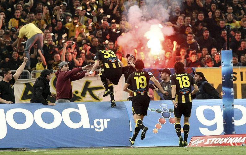 Jogadores do AEK comemoram a vitória do clube na final da Copa da Grécia. A equipe vivia um jejum de nove anos, e viu sua torcida entrar em uma confusão com a torcida logo após a conquista.