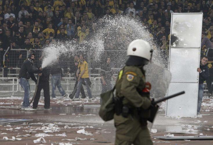 Torcedor usa jato d'água para afastar policiais durante a confusão que tomou conta do estádio Olímpico de Atenas após a Copa da Grécia, venida pelo AEK.