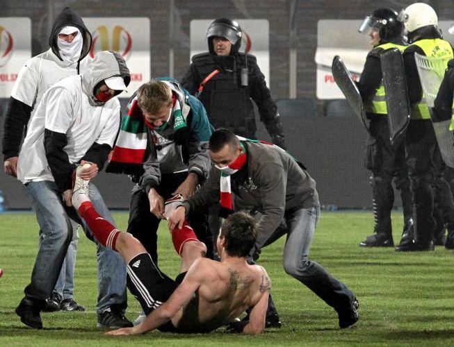 Torcedores do Legia Warsaw invadem o campo e perseguem os jogadores da equipe após a vitória por 5 a 4 nos pênaltis (após empate em 1 a 1)