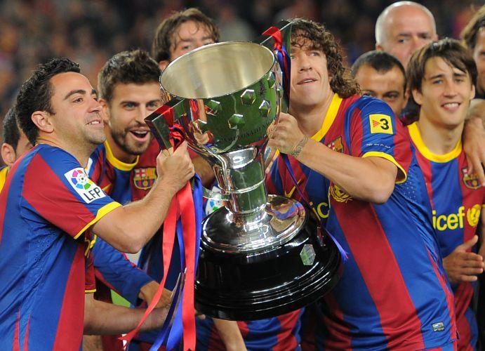 Puyol e Xavi erguem o troféu de Campeão Espanhol