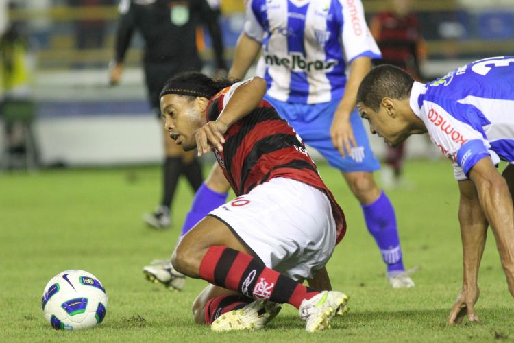 Ronaldinho se esforça para continuar jogada mesmo caído no gramado e diante da marcação de Fabiano. Flamengo e Avaí se enfrentam em Macaé