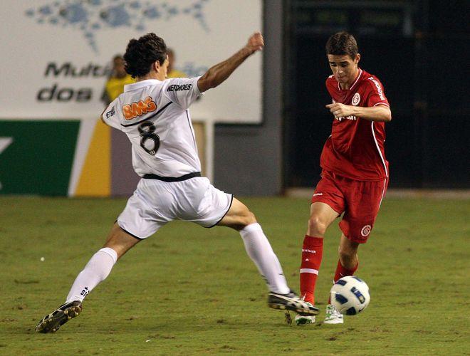 Meia do Inter, Oscar (d) tenta passar pela marcação do santista Rodrigo Possebon no empate por 1 a 1 na estreia das duas equipes no Brasileirão, em duelo na Vila Belmiro