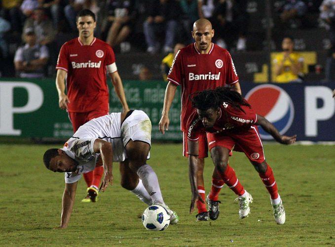 Observado por Bolivar (alto esq.) e Guiñazu (alto dir.), Tinga briga pela bola na estreia do Inter no Brasileirão contra os reservas do Santos, na Vila Belmiro