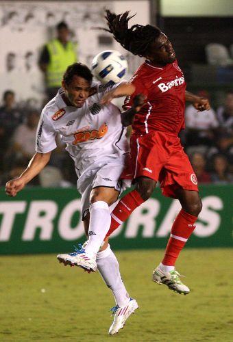 Tinga (d), do Inter, disputa jogada aérea na estreia do time no Brasileirão contra os reservas do Santos na Vila Belmiro