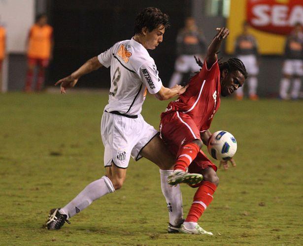 Tinga (d), do Inter, protege a bola de Rodrigo Possebon (e), do Santos, no empate por 1 a 1 na estreia dos times no Brasileirão, na Vila Belmiro