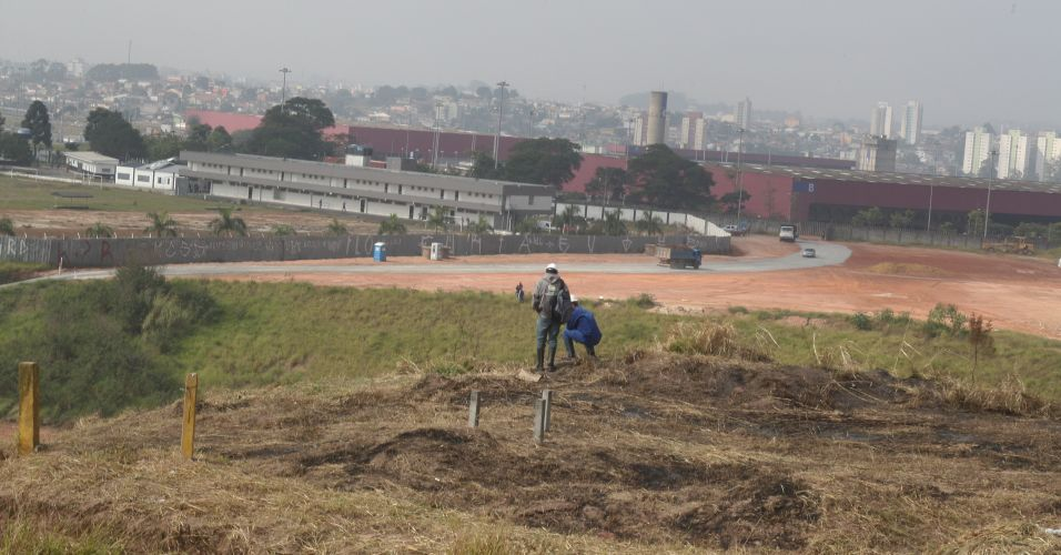 Funcionários trabalham na limpeza da área onde estão enterrados os dutos da Petrobras no terreno do estádio do Corinthians em Itaquera; tubos serão desviados para não atrapalhar as obras