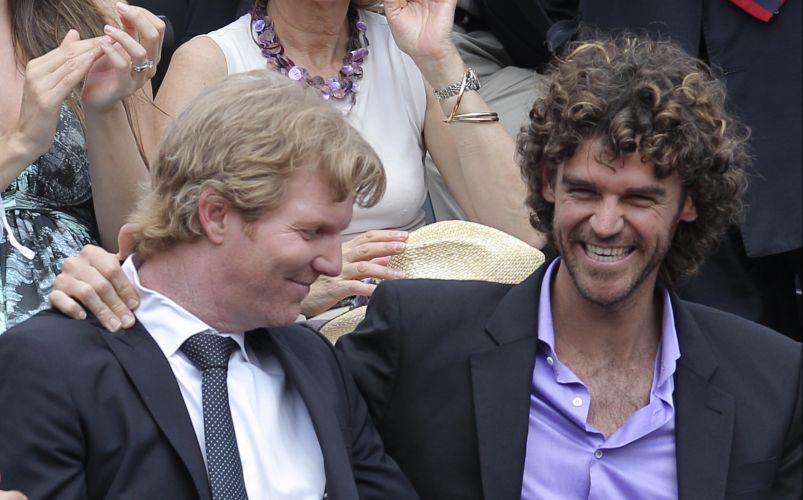 Ex-tenistas Jim Courier (e), dos Estados Unidos, e Gustavo Kuerten, do Brasil, se divertem na plateia da final de Roland Garros entre Rafael Nadal e Roger Federer