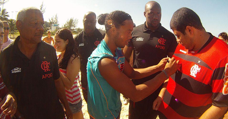 Ronaldinho Gaúcho autografa camisa de fã durante treino na Praia do Recreio