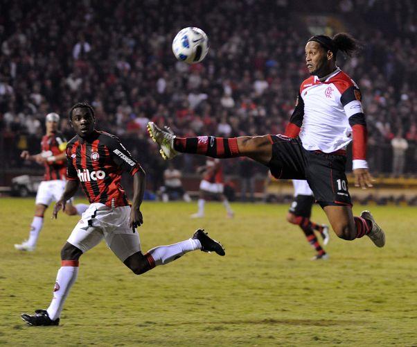 Ronaldinho Gaúcho se estica todo para dominar a bola, enquanto o zagueiro Manoel só observa