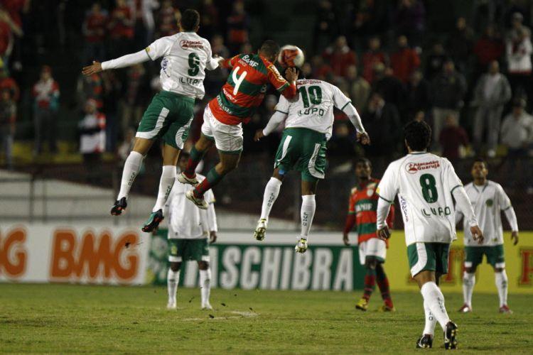 Jogadores disputam a bola pelo alto durante o jogo entre Portuguesa e Guarani no Canindé