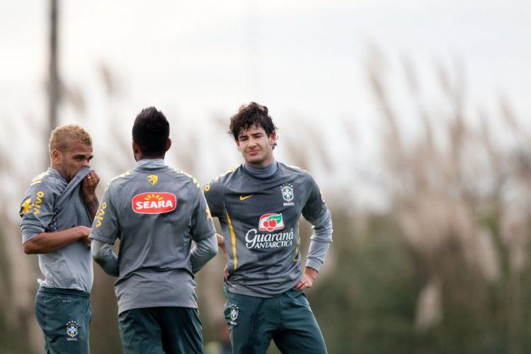 Daniel Alves, agora de cabelo pintado de loiro, conversa com Robinho e Alexandre Pato no treino da seleção.