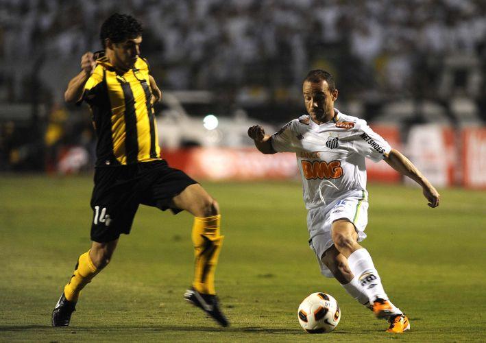 Léo tenta escapar da marcação de Luis Aguilar na decisão da Libertadores contra o Peñarol; Santos conquista o terceiro título da Libertadores e coroa geração de Ganso e Neymar