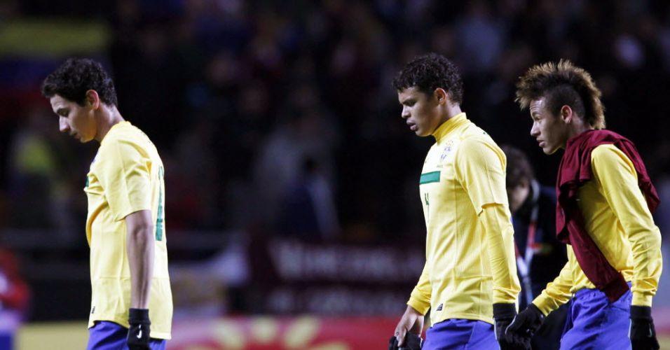 Ganso, Thiago Silva e Neymar saem cabisbaixos de campo após o empate sem gols do Brasil contra a Venezuela