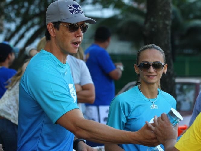 Observado pela líbero da seleção brasileira Fabi, ator Márcio Garcia distribui água durante a Maratona do Rio