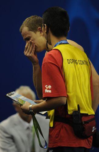 Ainda chorando depois de garantir o ouro nos 50m borboleta, Cesar Cielo é acompanhado por agente do comitê antidoping no mundial de xangai
