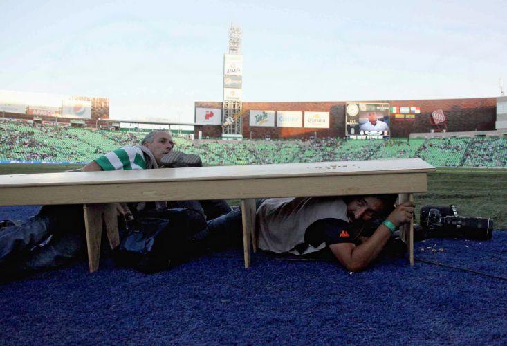 Fotógrafos se refugiam sob um banco para tentar proteger do tiroteio que ocorreu no estádio da cidade de Torreón, no México