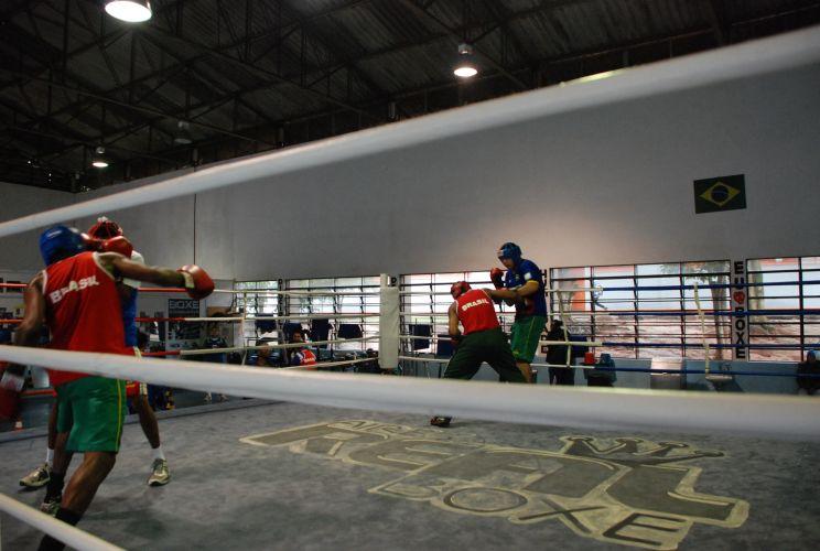 Atletas brasileiros praticam no ringue durante preparação em São Paulo.
