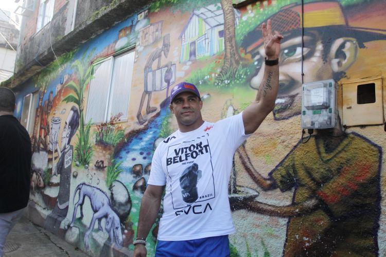 Vitor Belfort acena para os fãs em visita de lutadores ao Morro do Cantagalo, no Rio de Janeiro