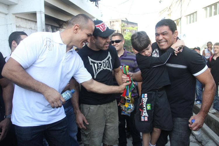 Júnior Cigano, Minotouro e Minotauro brincam com criança durante evento no Morro do Cantagalo