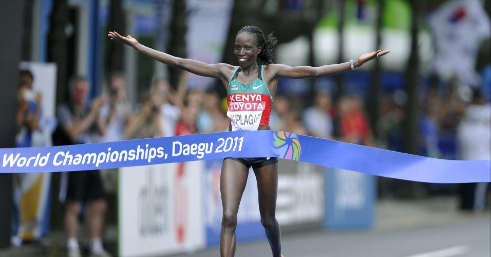 A queniana Edna Kiplagat abre os braços para festejar a vitória durante a chegada da maratona feminina