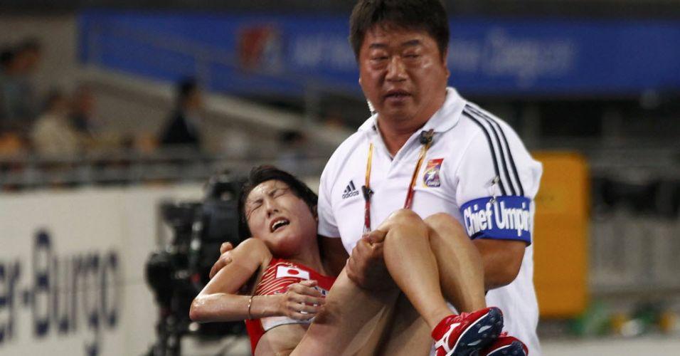 Membro da comissão técnica do Japão carrega Megumi Kinukawa após o fim da prova dos 10 mil metros