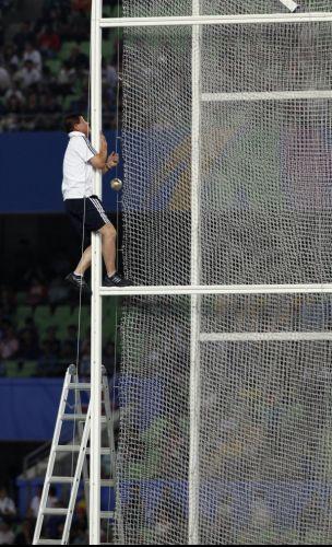 Voluntório sobe na rede para retirar martelo que ficou preso após arremesso no Mundial de Daegu