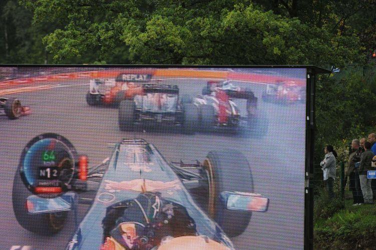 Pelo telão, espectadores acompanham a repetição do momento exato no qual Bruno Senna bate no carro de Jaime Alguersuari logo depois da largada do GP da Bélgica