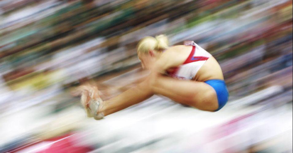 Russa Tatyana Chernova aterrissa no salto em distância para conquistar o ouro no heptatlo