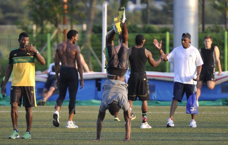 No meio de seus companheiros jamaicanos, Usain Bolt arrisca uma bananeira antes de iniciar seu treinamento no dia de folga do Mundial de atletismo.