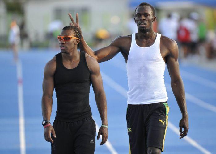 Aproveitando a presença dos fotógrafos, Usain Bolt faz chifrinho no seu amigo e rival Yohan Blake, também jamaicano, que venceu os 100m livre no Mundial de atletismo.