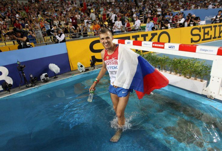O russo Aleksey Dmitrik comemora sua prata no salto em altura pulando no fosso dos 3.000m com obstáculos.