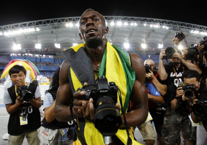 Jamaicano Usain Bolt pega câmera fotográfica após vencer os 200 m rasos