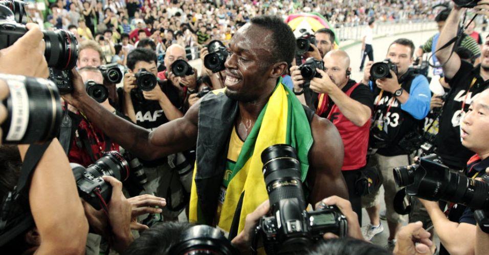 Usain Bolt brinca com os fotógrafos depois de conquistar o ouro no Mundial na prova dos 200 m rasos