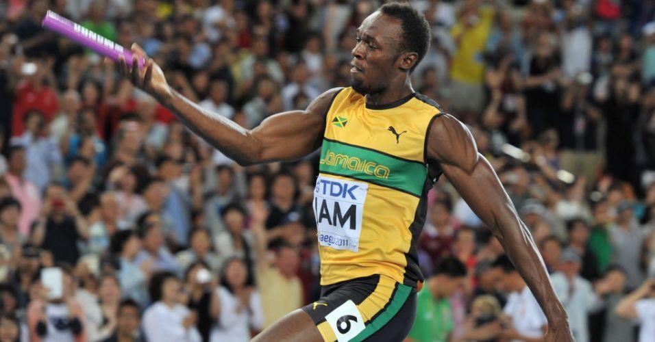 Usain Bolt corre com o bastão para vencer o revezamento 4x100 m pela equipe jamaicana