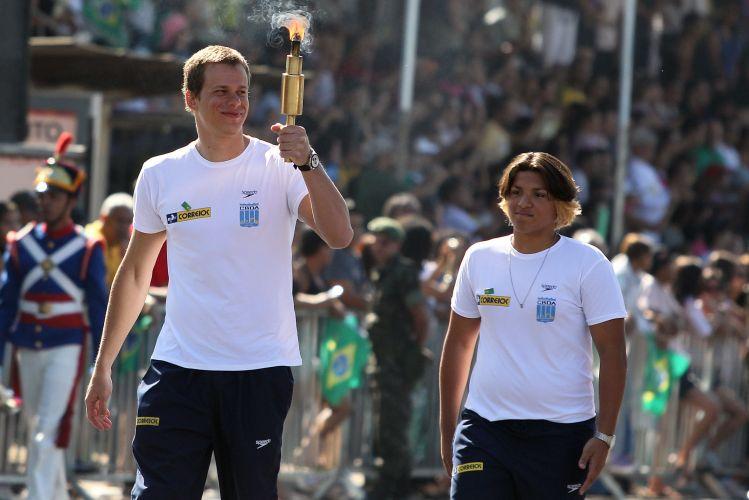 César Cielo e Ana Marcela Cunha, estrelas da natação brasileira, caminham em Brasília durante o desfile do dia da Independência, carregando a tocha do evento.
