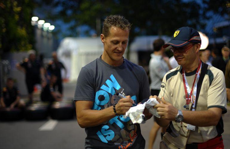 Michael Schumacher dá autógrafo enquanto caminha pelo paddock no circuito de Marina Bay
