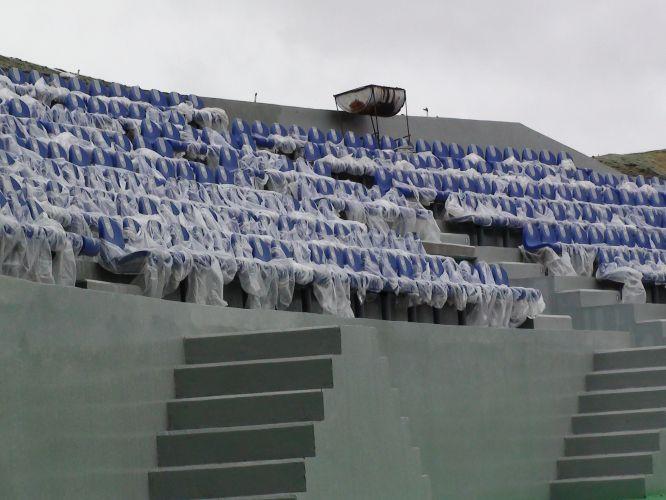 Cadeiras para os espectadores foram instaladas e ainda estão cobertas para enfrentar a chuva. Estádio tem capacidade para quase 9 mil pessoas