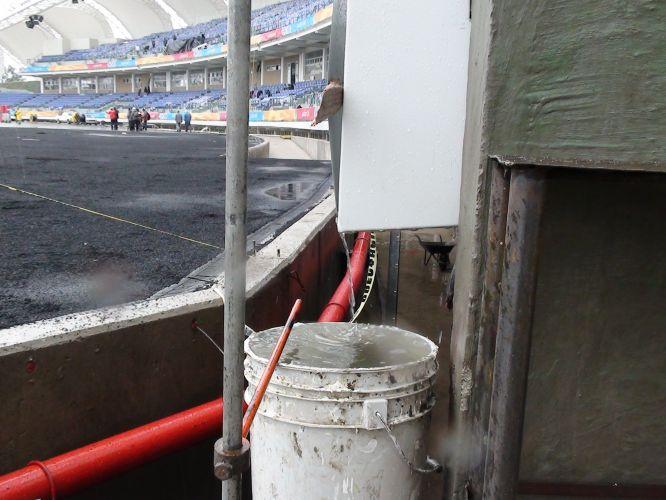 Chuva faz operários improvisarem um balde como calha na parte interna do estádio Telmex