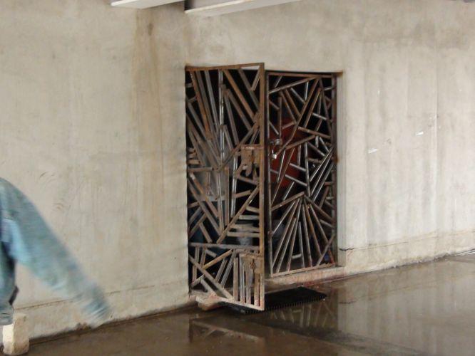 Porta feita com pedaços de canos enferrujados ainda carece de pintura em acesso inferior do estádio Telmex