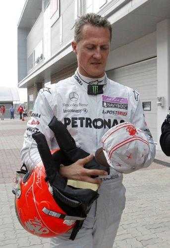 Michael Schumacher volta a pé para os boxes após abandonar o GP da Coreia do Sul. Vitaly Petrov, da Renault, bateu na Mercedes do piloto alemão