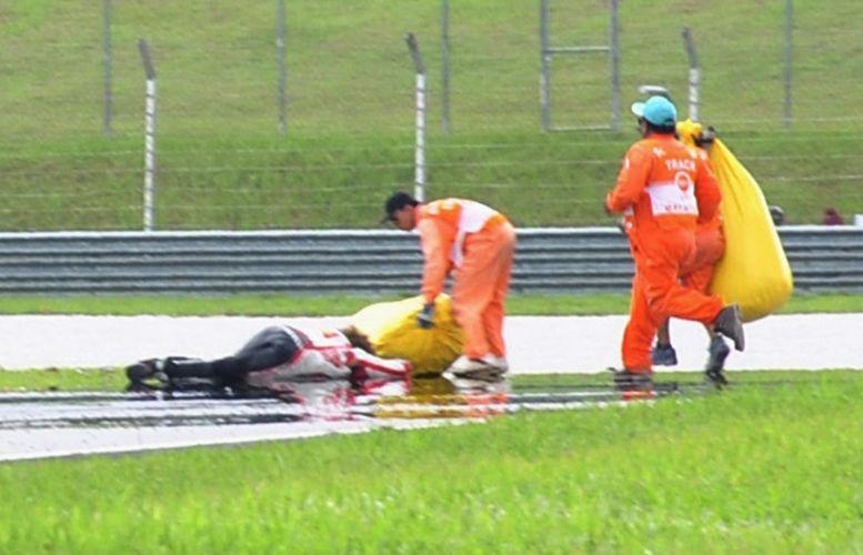 Fiscais atendem Marco Simoncelli, que ficou de bruços na pista após sofrer gravíssimo acidente no GP da Malásia de MotoGP. Piloto não resistiu aos ferimentos e morreu (23/10/2011)