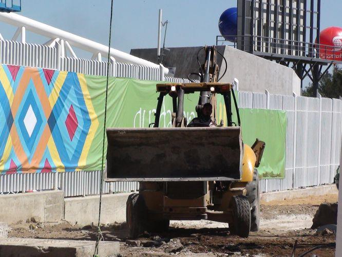 Tratores se movimentam perto da entrada principal do estádio e carregam materiais de construção