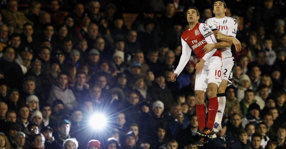 Torcedor usa flash para fotografar jogada com Van Persie e Stephen Kelly durante jogo entre Arsenal e Fulham