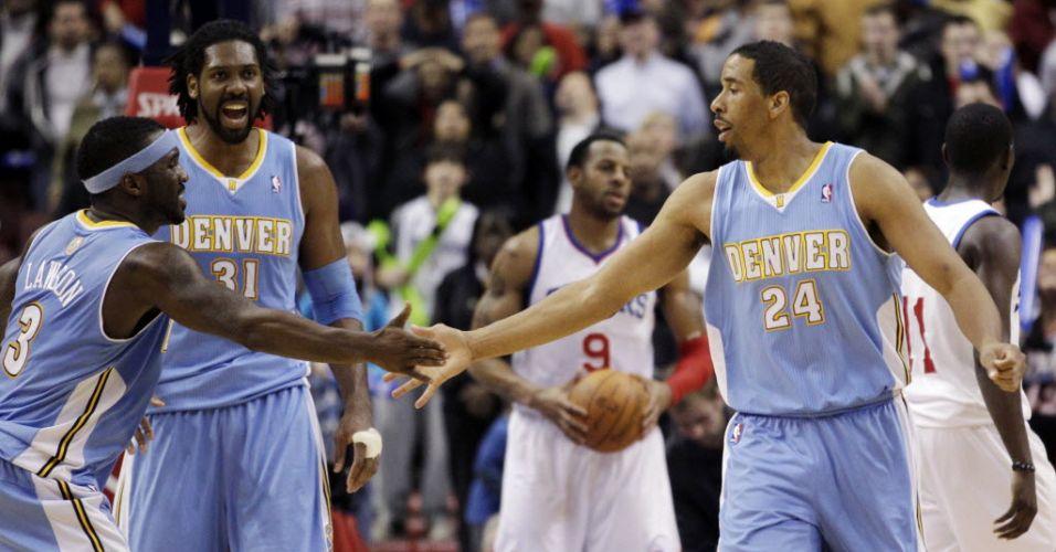 Cestinha da vitória dos Nuggets sobre os Sixers, Andre Miller(d) cumprimenta Ty Lawson observado por Nenê, líder em rebotes na equipe