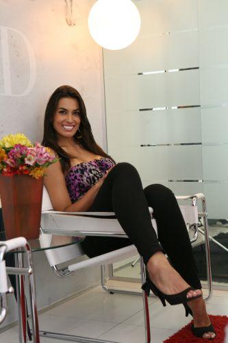 Luciane posa sorridente dentro da agência Ford Models. A jogadora ganhou um concurso de beleza no Rio Grande do Sul e concilia a vida de modelo com o vôlei.