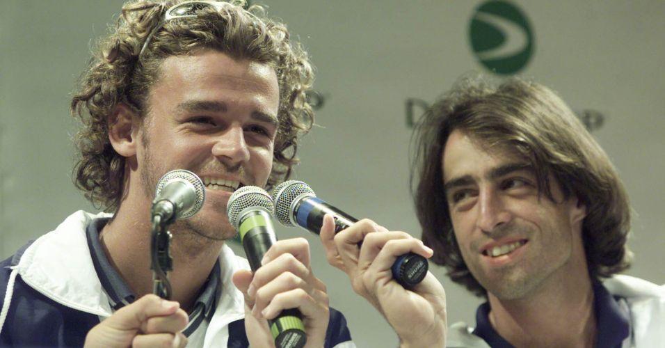 Guga e Fernando Meligeni brincam com microfones durante sorteio dos jogos em confronto da Copa Davis de 2000, ano em que a equipe brasileira igualou sua melhor campanha ao alcançar a semifinal